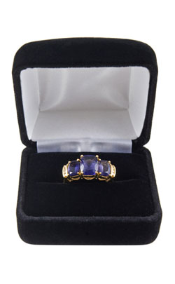 Iolite ring in a blue jewellery cushioned case indicating the type of gifts that can be purchased for the 21st year wedding anniversary