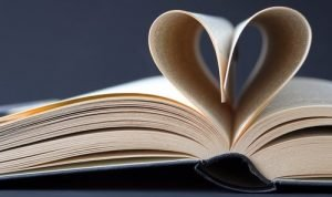 Book with pages folded into a love heart shape to represent research for the history