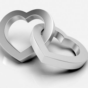 Two silver metal lovehearts intertwined seamlessly